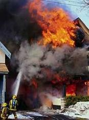 Fireman extinguishing large house fire